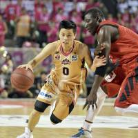 Try and keep up: Akita's Yuki Togashi drives around a Toyama defender during their Final Four matchup on Saturday. Akita won 109-94. | KYODO