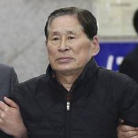 Kim Han-sik, president of Chonghaejin Marine Co. Ltd., which owns the sunken ferry Sewol, is escorted by helpers to hold a press conference at Incheon Port International Passenger Terminal in Incheon, South Korea, on April 17. On Friday, Kim was arrested after investigators raised suspicions that improper stowage and overloading of cargo might have contributed to the accident. | AP