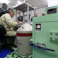 A device is used to detect and analyze radioactive materials in fish samples as a researcher inputs data at Marine Ecology Research Institute's central laboratory in Onjuku, Chiba Prefecture, last December. | BLOOMBERG