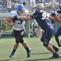 Pressure on the quarterback: Obic defensive tackle Yoshihiro Nakada rushes IBM quarterback Kevin Craft, forcing him to scramble during the second quarter. Craft was held to one touchdown pass in the game. | HIROSHI IKEZAWA