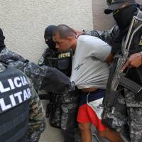 Members of the military police escort suspected Honduran drug lord Carlos Arnoldo Lobo, also known as 'Negro Lobo,' to the Supreme Court in Tegucigalpa on March 28. Lobo will be extradited to the U.S., where he is wanted for drug trafficking, on Thursday. | AFP-JIJI