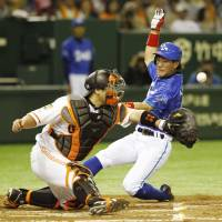 He beats the throw: The BayStars' Sho Aranami scores on Takehiro Ishikawa's second-inning single against the Giants on Tuesday at Tokyo Dome. Yokohama beat Yomiuri 2-1. | KYODO