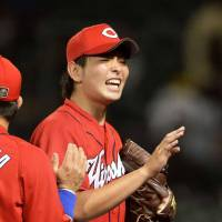 On my own: Carp rookie pitcher Daichi Osera (center) is congratulated by his teammates after recording his first complete-game victory on Thursday against the Tigers. | KYODO