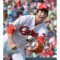 No time to lose: Hiroshima starter Ken Maeda makes a throw to first after catching a bunt during the Carp's 5-2 win over the BayStars on Sunday. | KYODO