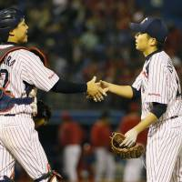 Just doing my job: Swallows pitcher Masanori Ishikawa (right) is congratulated by catcher Yuhei Nakamura after throwing a shutout against the Carp on Wednesday at Jingu Stadium. | KYODO