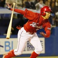 Late insurance: Carp pinch hitter Naoki Nakahigashi belts a three-run double in the ninth inning against the Swallows on Thursday at Jingu Stadium. Hiroshima defeated Tokyo Yakult 13-7. | KYODO