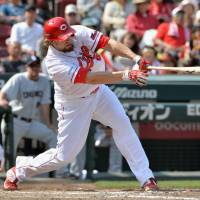 See you later: Hiroshima's Brad Eldred puts the Carp ahead in the third inning of their 13-5 win over the Dragons on Saturday. | KYODO