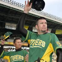 Center of attention: Tigers hurler Randy Messenger (right) tips his cap to the fans after Hanshin's 1-0 win over the Yomiuri Giants on Sunday at Koshien Stadium.   KYODO