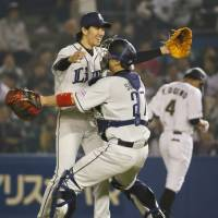 Sharing history: Lions catcher Ginjiro Sumitani embraces pitcher Takayuki Kishi after the latter tossed a no-hitter on Friday against the Marines. | KYODO
