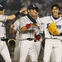 Happy finish: Lions teammates congratulate Takayuki Kishi after Friday's game ended. | KYODO