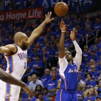Dynamic performance: Clippers guard Chris Paul launches a shot in front of Thunder guard Derek Fisher in the second quarter of Game 1 of the Western Conference semifinals in Oklahoma City on Monday. Paul finished with 32 points and 10 assists in Los Angeles' 122-105 victory over Oklahoma City. | AP