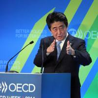Prime Minister Shinzo Abe addresses the OECD assembly in Paris on Tuesday during his six-nation European tour for trade and security talks. | AFP-JIJI