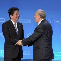 Prime Minister Shinzo Abe shakes hands with OECD Secretary General Angel Gurria after addressing the OECD assembly Tuesday at the OECD headquarters in Paris. | AFP-JIJI