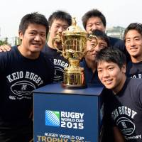 Iconic symbol: Keio University rugby team members pose with the Webb Ellis Cup, the winner's trophy for the upcoming 2015 Rugby World Cup, during a kick-off event of the trophy tour in Yokohama on Friday. | AFP-JIJI
