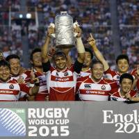 See you in England: Japan captain Michael Leitch lifts the trophy as the Brave Blossoms celebrate their win over Hong Kong on Sunday. Japan claimed the Asian Five Nations title and a spot in the 2015 Rugby World Cup with the win.   AP