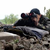 An armed pro-Russian fighter takes position at a checkpoint near the eastern Ukranian city of Slavyansk on Monday. Russia raised the stakes in the Ukraine crisis by saying it respected what rebels claimed was a resounding vote in favor of self-rule in the east of the country. | AFP-JIJI