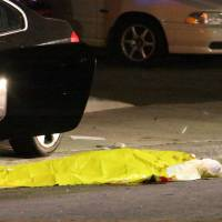 A body lies on the ground after a mass shooting near the campus of the University of California, Santa Barbara, in Isla Vista late on Friday night. A drive-by shooter went on a 'mass murder' rampage near the campus that left seven people dead, including the attacker, and seven others wounded, authorities said Saturday. | AP
