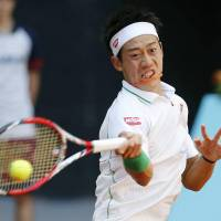 Early success: Kei Nishikori hits a return to Croatia's Ivan Dodig in the first round of the Madrid Open on Monday. Nishikori advanced with a 6-4, 6-4 win. | KYODO