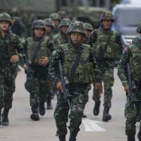 Thai soldiers run to stand guard after Thai Army Gen. Prayuth Chan-ocha met with anti-government and pro-government leaders at the Army Club in Bangkok on Thursday. Thailand's army chief announced in an address to the nation the same day that the armed forces were seizing power after months of deadly political turmoil. | AFP-JIJI