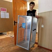 An election commission worker carries a ballot box at a polling station for Sunday's referendum in the eastern Ukrainian city of Lugansk on Saturday. | REUTERS