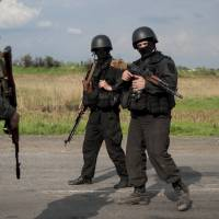 Ukrainian National Guard soldiers guard a checkpoint outside of Slovyansk in eastern Ukraine on Sunday. Ukrainian Interior Minister Arsen Avakov said in a statement on his Facebook page that an 'antiterrorist operation' was being executed in the eastern city of Kramatorsk, the latest flashpoint for unrest. | AP
