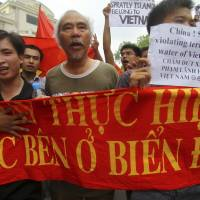 Vietnamese protesters carry a banner with a Vietnamese slogan reading, 'China must respect and execute the Declaration on the Conduct of Parties in the South China Sea,' during a protest in June 2011 demanding that China stay out of their waters following an increase in Chinese maritime activity around the Spratly Islands and other disputed areas, in Hanoi. | AP