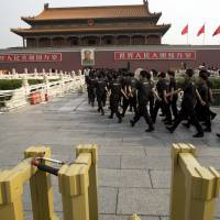 Security guards march Saturday past the site where a man crashed an SUV and set the vehicle on fire after mowing down a crowd of tourists in front of Tiananmen Gate, Beijing, on Oct. 28. | AP
