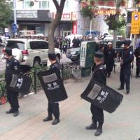 Chinese police stand guard near a blast site that has been cordoned off in downtown Urumqi, the capital of the Xinjiang Uygur Autonomous Region, on Thursday. | XINHUA/AP