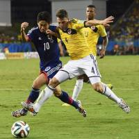 Colombia's Santiago Arias vies for the ball with Japan's Shinji Kagawa. | REUTERS