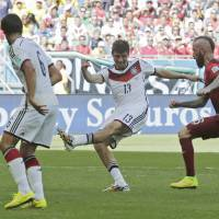 Germany's Thomas Mueller (second from right)  scores his side's third goal during Monday's match against Portugal at the Arena Fonte Nova in Salvador, Brazil,  | AP