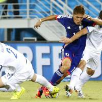 Japan striker Yoshito Okubo vies with Greece defenders during Thursday's Group C match against Greece.  | KYODO