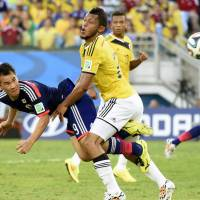 Japan's Shinji Okazaki scores an injury-time equalizer during Tuesday's Group C match against Colombia in Cuiaba. | KYODO
