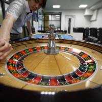 An employee works the roulette wheel at the Japan Casino School in Tokyo on June 16. Anticipation that a bill to legalize casinos will pass the Diet helped the school enroll about 60 students in April, the second most since it was launched in 2004. | BLOOMBERG