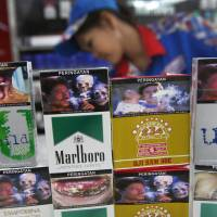 New packs of cigarettes displaying pictorial health warnings are arranged on the counter at a Jakarta convenience store Tuesday. Tobacco firms on Tuesday largely snubbed an Indonesian law requiring them to put graphic photo warnings on all packs being sold, marking another setback in a country that's home to the world's highest rate of male smokers. | AP