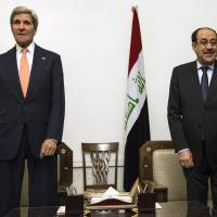 U.S. Secretary of State John Kerry (left) stands with Iraqi Prime Minister Nouri al-Maliki at the prime minister's office in Baghdad on Monday, where Kerry met with Iraq's leaders and urged the Shiite-led government to give more power to political opponents before a Sunni insurgency seizes further territory and threatens government authority. |  AP