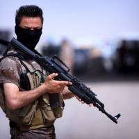 A Pershmerga fighter from Iraq's autonomous Kurdish region guards a camp set up to shelter Iraqis fleeing violence in northern Nineveh province, on June 13. | AFP-JIJI