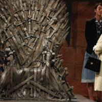 "Britain's Queen Elizabeth examines the Iron Throne from the television show ""Game of Thrones,"" which is filmed at a studio in Belfast's Titanic Quarter. She visited the show's set Tuesday. 