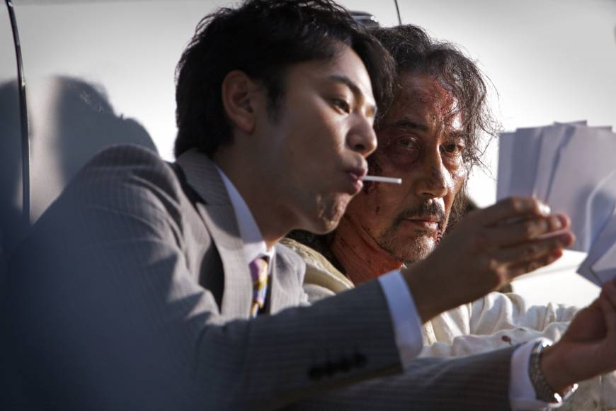 Hiding secrets: Akikazu Fujishima, played by Koji Yakusho (right), on the path of his hedonistic daughter, is approached by his former colleague, a lollipop-licking cop named Asai (Satoshi Tsumabuki).