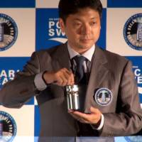 Astroscale founder Nobu Okada, speaking May 15 at Tokyo Skytree Town, holds a 'dream capsule' that looks like a can of Pocari Sweat. He plans to send the capsule to the moon to raise funds for an effort to clean up lower Earth orbits. | KAZUHIRO KOBAYASHI