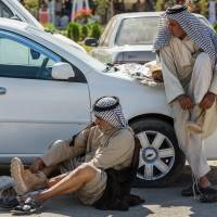 Members of an Iraqi volunteer force put on their newly issued boots in the Shiite holy city of Karbala, 80 km south of Baghdad, on Tuesday.   AP