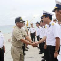 A Philippine Navy officer greets his Vietnamese counterparts upon arrival Sunday on Southwest Cay in the disputed Spratly Islands. | REUTERS