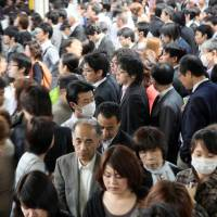 Commuters make their way slowly through a crowded train station in Tokyo in May 2011. | BLOOMBERG