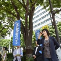 Yoko Mitome, a former temporary contract worker for KDDI Corp. (right), speaks during a protest outside the company's headquarters in Tokyo on May 23. | BLOOMBERG
