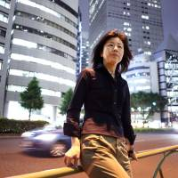 Miho Marui, a former contract employee at KDDI Evolva Inc., poses in front of the KDDI building in Tokyo's Shinjuku district on May 26. Marui is battling with Japan's second-largest phone company over labor practices at one of its subsidiaries.   BLOOMBERG