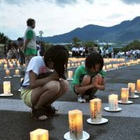 Mourners pray on Tuesday for those killed when Mount Unzen erupted in 1991 above Shimabara, Nagasaki Prefecture.   KYODO