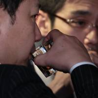 Men sip Jack Daniel's whiskey at the liquor maker's official bar in Tokyo in January. | BLOOMBERG