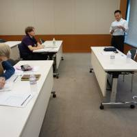 Masashi Miyagawa, manager at Acroseed Co., a Tokyo-based company providing consulting services on foreign worker-related matters, leads a seminar for foreigners interested in starting a business here in Tokyo on June 6. | KAZUAKI NAGATA