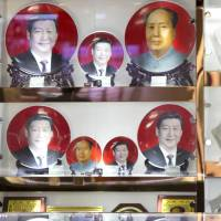 A vendor sells plates with images of Chinese President Xi Jinping and late leader Mao Zedong in Beijing on June 4. Xi's anti-graft campaign is now targeting officials who have sent their spouses and children abroad, creating channels to funnel illicit gains. | AP
