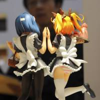 A visitor to the Tokyo International Anime Fair looks at cartoon figures on display. The Diet passed a law on Wednesday that bans possession of child pornography but excludes sexually explicit depictions of children in manga, anime and computer graphics. | AP