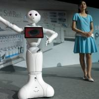 Pepper, Softbank's new 'emotion-reading' robot, shows off a dance move at a demonstration booth in Urayasu, Chiba Prefecture. | KAZUAKI NAGATA